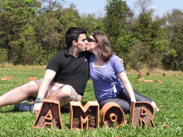 Casal se beijando com letras AMOR em frente