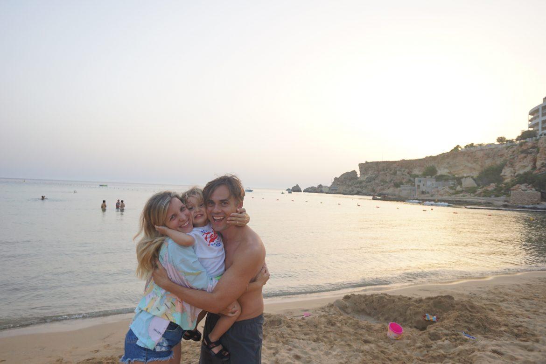 pais abraçando filho com mar ao fundo em Malta
