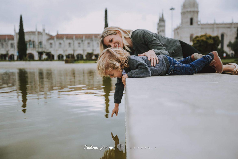 mãe e filho olhando espelho d´água enquanto ele tenta tocá-lo